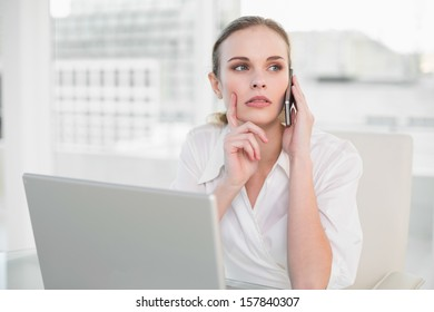 Thoughtful businesswoman using laptop and making a call in her office