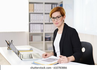 Thoughtful businesswoman working on an open binder at her desk in the office looking across the room with a pensive serious expression