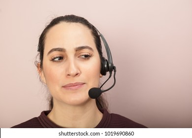 Thoughtful call center operator listening to a call looking to the side with a pensive expression and quiet knowing smile
