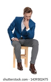 Thoughtful casual man holding his hand on his chin and looking down while wearing a suit and sitting on a chair on white studio background