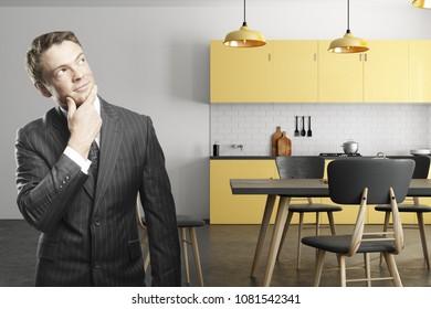 Thoughtful caucasian businessman standing in modern kitchen interior. 3D Rendering