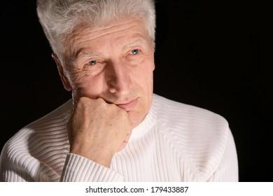 Thoughtful caucasian elder man on black background