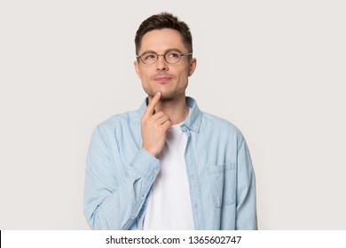 Thoughtful Caucasian young male in glasses touch chin with finger thinking or considering, pensive European man wearing spectacles isolated on grey studio background making decision or imagining