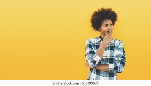 Thoughtful charming black teenage female in plaid shirt with curly afro hair on yellow background, reflective young biracial girl looking aside, with copy space for text or your logo