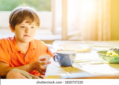 Thoughtful child boy wearing orange t-shirt with down syndrome sitting at table at home. Sun glare effect. Special needs children concept.