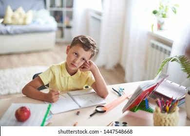 thoughtful child sits at a table with textbooks and educational supplies.student dreams and looks to the top. scattered attention of the student. problems of concentration and assimilation information
