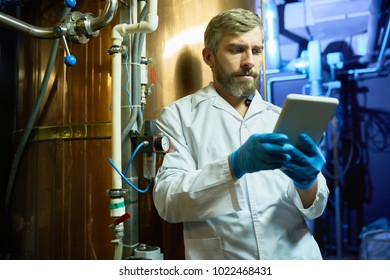Thoughtful concentrated brewing technician in lab coat using digital tablet while learning specialties of brewery machinery at plant