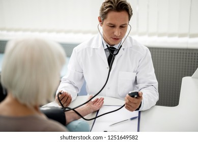Thoughtful concentrated general practitioner sitting in front of his patient with stethoscope and measuring her blood pressure