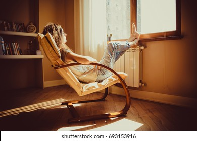 Thoughtful concept. Sad woman lost in thought lounging in comfortable modern chair looking at window in livingroom. Warm natural light. Cozy home. Casual style indoor. Room interior. Tired woman.