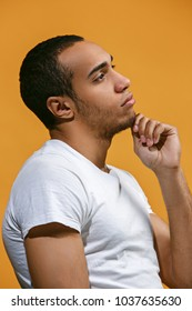Thoughtful concept. Satisfy Afro-American man is looking thoughtfully. Young emotional man. Human emotions, facial expression concept. Profile . Studio. Isolated on trendy orange