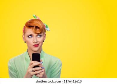 Thoughtful confused upset puzzled woman pinup girl looking up holding her smart phone isolated yellow background retro vintage 50's hair style. Human emotions body language