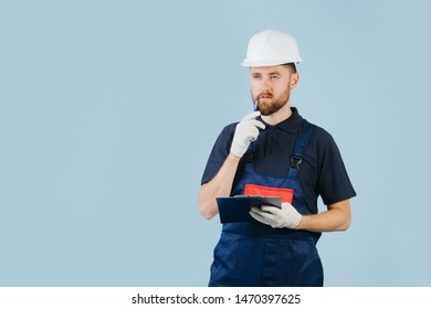 Thoughtful construction engineer in a white helmet and dark blue uniform with a paper schematics, stroking beard with a pen, calculating something in mind.