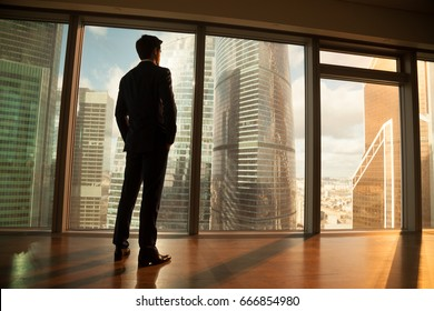 Thoughtful contemplative businessman wearing suit standing back holding hands in pockets, looking out of big window at city buildings, gets inspiration for business project, enjoys sunset, rear view