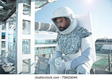 Thoughtful cosmonaut is sitting on bench and looking forward with pensive sight. Waist up portrait. Copy space on left side