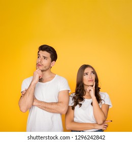 Thoughtful couple thinking and touching chin over yellow background with copy space