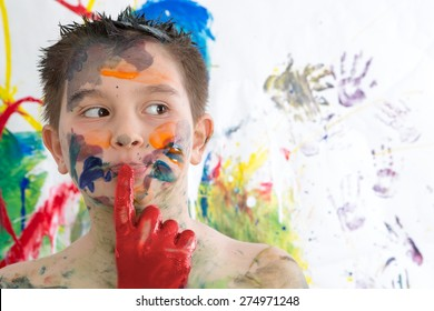 Thoughtful creative little boy covered in paint standing with his finger to his lips looking contemplatively to the side in front of his contemporary artwork as he seeks inspiration