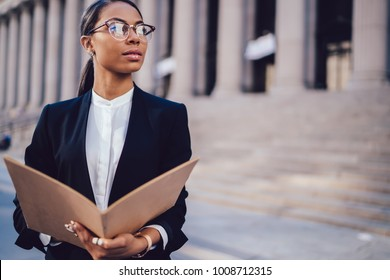 Thoughtful dark skinned female financial manager in black suit holding folder in hands while standing against office building outdoors. African American student of high financial economist university