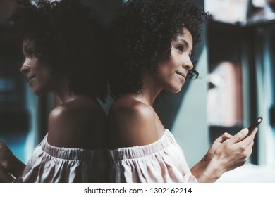 A thoughtful dazzling young biracial female leaning against the mirror wall outdoors and looking pensively in front while holding her smartphone in hands and texting a friend on a warm summer day