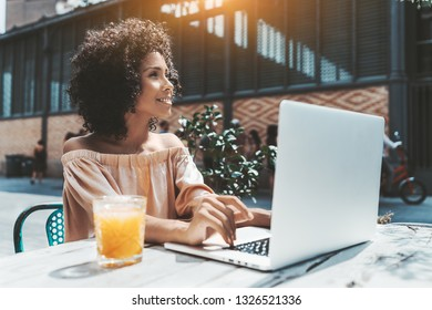 A thoughtful dazzling young Brazilian female is pensively looking at something in a distance while sitting in a street bar with her laptop and working on a freelance project, a glass of juice near her