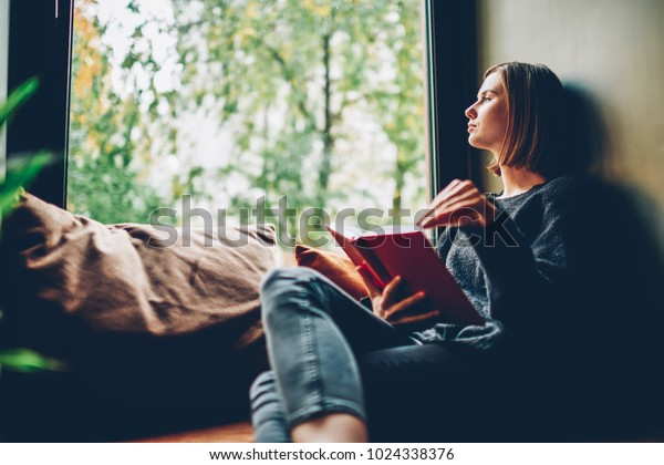 Thoughtful depressed alone young woman looking out of window pondering on idea and plot of new bestseller of favourite author resting on comfortable windowsill in stylish coworking space