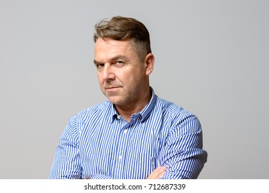 Thoughtful determined middle aged man standing staring at the camera with folded arms and a speculative expression