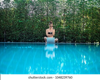 thoughtful digital nomad girl sitting & reflecting at the pool with her laptop