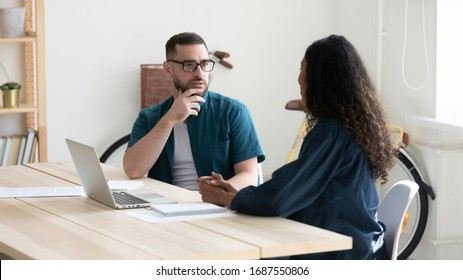 Thoughtful diverse colleagues sit at desk in office talk discuss business ideas at briefing together, pensive businesspeople brainstorm cooperate using laptop at meeting, collaboration concept