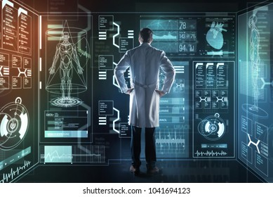 Thoughtful doctor. Qualified experienced smart doctor standing in front of a futuristic device and thoughtfully looking at it while working