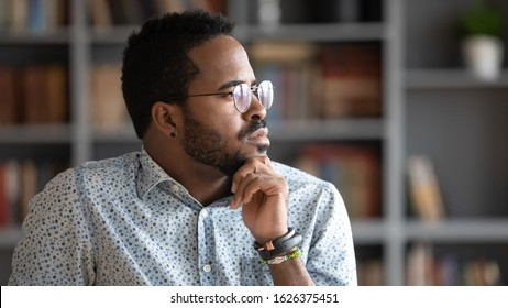 Thoughtful doubtful african american businessman wear glasses looking away thinking of problem solution future challenges, serious ethnic man profile face feel uncertain lost in thoughts concept