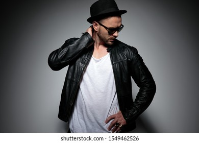 Thoughtful dramatic man holding his hands behind his head and on his waist while wearing a black hat and sunglasses, standing on gray studio background