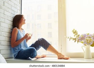 Ein gedankenvolles und träumendes Mädchen, das aus dem Fenster einer belebten Stadt schaut, während es auf der Fensterbank sitzt und eine Tasse aromatischen Kaffee hält