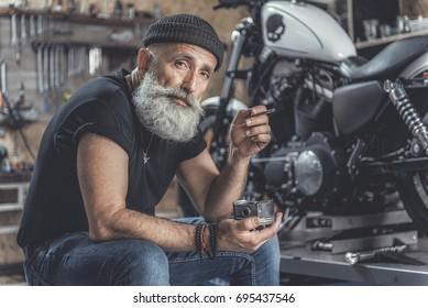 Thoughtful elder man locating nearby motorbike