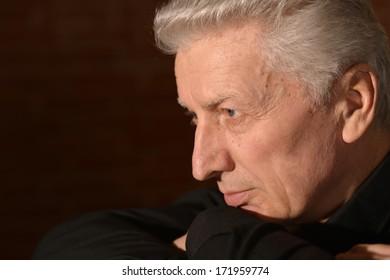 Thoughtful elder man on black background