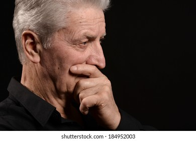 Thoughtful elder man on a black background