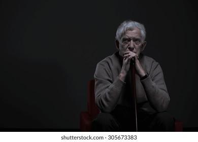 Thoughtful elder man sitting in a dark room