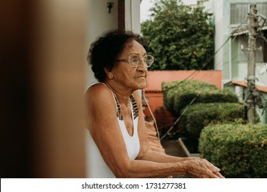 thoughtful elderly Brazilian woman on her home's balcony during quarantine - slow motion
