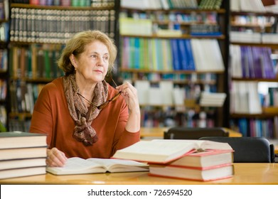 Thoughtful elderly woman in library. Space for text