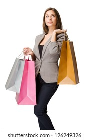 Thoughtful elegant young brunette woman with colorful shopping bags.
