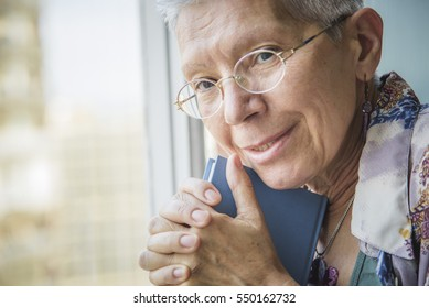 Thoughtful and emotional portrait of an old senior woman holding a book in her arms