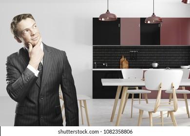 Thoughtful european businessman standing in modern kitchen interior. 3D Rendering
