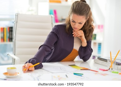 Thoughtful fashion designer working in office