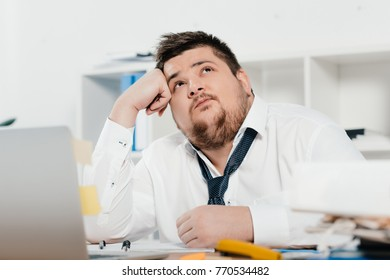 thoughtful fat businessman with laptop at workplace in office