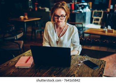 Thoughtful female copywriter concentrated on task earning money online using modern laptop, thinking businesswoman making research on web pages solving problems doing remote job in cafe interior