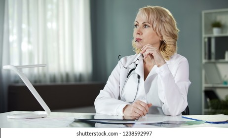 Thoughtful female doctor sitting at table, analysing patient results, diagnosis