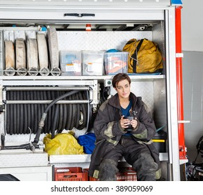Thoughtful Firewoman Holding Coffee Mug In Truck