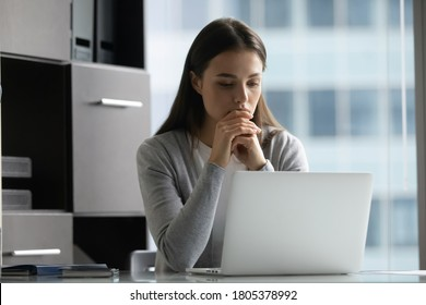 Thoughtful focused businesswoman looking at laptop screen, sitting at desk in modern office, young woman employee worker working on difficult project, pondering strategy, reading email