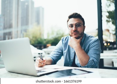 Thoughtful freelance bookkeeper sitting at table with laptop and documents and writing while supporting head with one hand and looking at camera