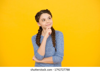 thoughtful girl with braids. adorable daydreaming kid. think about future. Portrait of pensive teen girl on yellow background. Let me think. Doubt concept. Doubtful child remembering something.