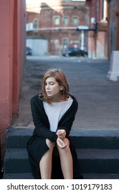 A thoughtful girl in a long black cardigan and short shorts is sitting on the steps