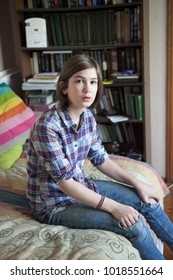 A thoughtful girl in a plaid shirt is sitting on the bed in front of a bookcase